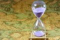 Hourglass sandglass sand timer sand clock on ancient map background Royalty Free Stock Images