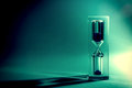 Hourglass sandglass  with shadows and glare of the sun on a dark background. Old retro style vintage photo. Royalty Free Stock Photo