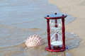 Hourglass with seashell on seashore Royalty Free Stock Photo