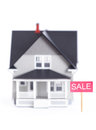 House architectural model with sale sign, isolated Royalty Free Stock Photos