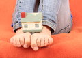 House on base from bare feet of a little girl child sitting sofa with orange cover Stock Photography