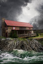 House being flooded a farm with a red roof on the edge of an eroded area of farmland with raging flood waters passing by concept Stock Photos