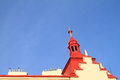 House with belfry roof of red and blue sky behind Stock Photos