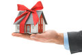 House in businessman s hand real estate agent holds architectural model with red bow Royalty Free Stock Photos
