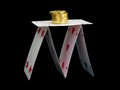 House of cards with gold coins on black background Stock Photos