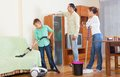 House cleaning middle aged couple with teenage son doing at home Stock Images