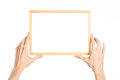 House decoration and Photo Frame topic: human hand holding a wooden picture frame isolated on a white background in the studio fir