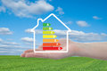House and energy efficiency graph on hand blue sky meadow in background Stock Photos