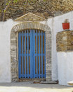 House entrance in a mediterranean island blue door and flowerpot Royalty Free Stock Images