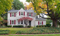 House in fall with red shutters large luxurious and colorful foliage Royalty Free Stock Images