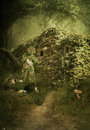 House in the forest maisonette ivy covered and magical woodsman with a bucket of water pours mushrooms Stock Photo