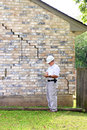 House foundation damage inspector inspecting home's is experiencing settlement collapse eventually the brick veneer begins to Royalty Free Stock Photography