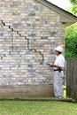 House foundation damage inspector inspecting home's is experiencing settlement collapse eventually the brick veneer begins to Royalty Free Stock Images