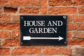 House and garden sign attached to an old red brick wall Stock Photo
