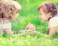 House in hands happy children holding model kids lying on green grass spring park new home concept Stock Images