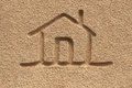 House home icon or sign drawing in beach sand concept photo this shows a hand written symbol with door and roof drawn Royalty Free Stock Photos