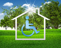 House icon with handicap symbol green grass and blue sky as backdrop Stock Photography