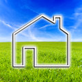 House icon on virtual screen with background of beautiful meadow and blue sky Stock Photos