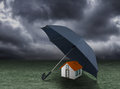 House insurance concept, house protected under umbrella Royalty Free Stock Photo