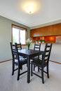 House interior. Simple black dining table set in small dining room with view of the kitchen.