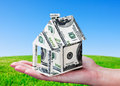 House made of money in hand on background of green field Stock Images