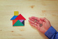 House made from tangram puzzle and key over wooden table Royalty Free Stock Photo