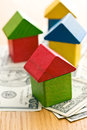 House made from wooden toy blocks on dollars the Royalty Free Stock Photos