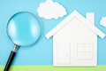 House and magnifier on paper background. Royalty Free Stock Photo