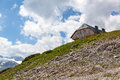 House in the mountains at a slope with rocks and scree Royalty Free Stock Image