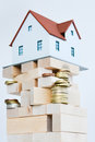 House ownership concept – a model house on a pile of coins Royalty Free Stock Photo
