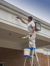 House painter finishing off the soffit on a commercial building Stock Images