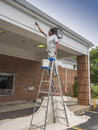 House painter finishing off the soffit on a commercial building Royalty Free Stock Photography