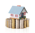 House placed on a pile of gold coins on white background Royalty Free Stock Photo