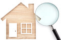 House shaped paper cutout and magnifier on natural wood lumber. Royalty Free Stock Photo