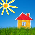 House and sun on the background of green grass  and blue sky Royalty Free Stock Photos