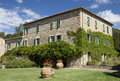House in tuscany stone with creeping ivy on the facade lawn and big ceramic vases the front Royalty Free Stock Photography