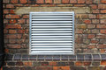 House ventilation grill on brick wall facade Stock Photo