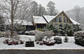 House in winter snow the front yard of a large home with falling Stock Images