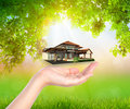 House on woman hand over Green leaf Royalty Free Stock Photo
