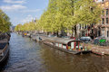 Houseboats on a canal in amsterdam the netherlands Stock Photos