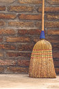 Household broom for floor cleaning leaning on brick wall used dust vertical Stock Photo