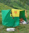 Household green-yellow tent with things in a forest glade during a wild outdoor recreation in summer. Bunches of fragrant Royalty Free Stock Photo