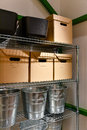 Household storage plastic containers carton boxes and metal buckets in a room on the shelves Stock Photography