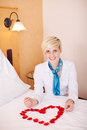 Housekeeper arranging petals in heart shape on bed portrait of happy female Royalty Free Stock Image