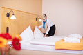 Housekeeper making bed in hotel room young blond hair Royalty Free Stock Image
