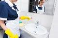 Housekeeper spraying a hand basin