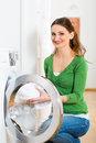 Housekeeper with washing machine young woman or has laundry day at home she takes the out of the or the dryer Royalty Free Stock Photography
