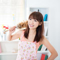 Housekeeping happy asian housewife with apron hand holding a duster and smiling young woman indoors living lifestyle at home Royalty Free Stock Image