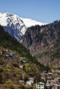 Houses with snow covered mountains in the background manali hima town himachal pradesh india Stock Photos
