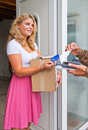 Housewife accepting package young a cash on delivery from a courier paying with her debit card Stock Photos